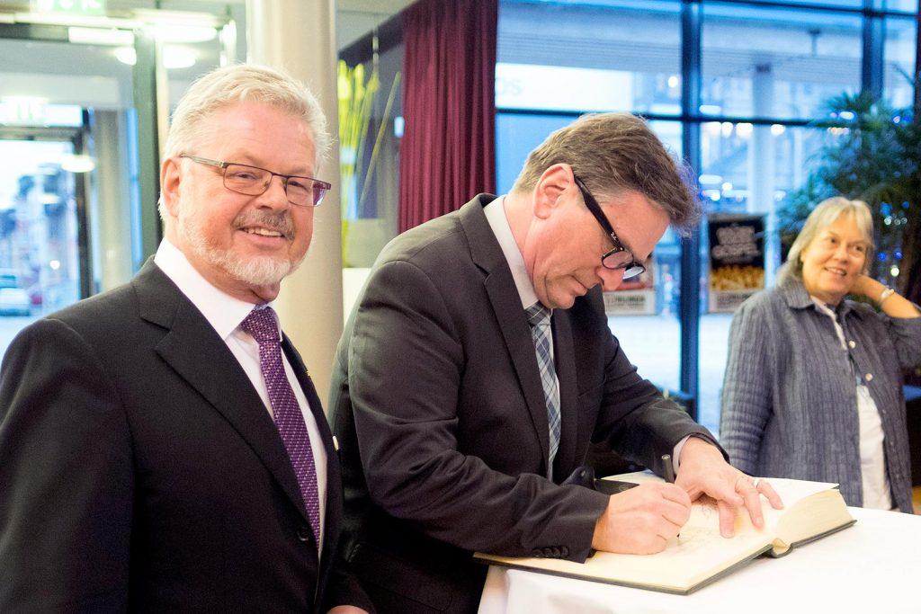 Minister Manfred Lucha trägt sich ins Goldene Buch der Nachsorgeklinik Tannheim ein. Links Tannheim-Geschäftsführer Roland Wehrle.