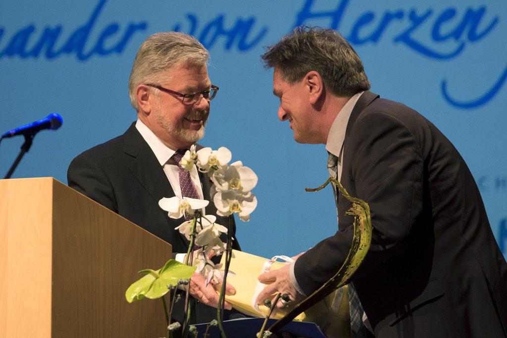 Eine Tannheim-Uhr von Otmar Alt wird überreicht, Abschiedsgeschenk an Minister Lucha.