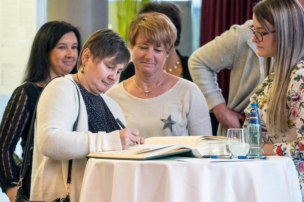 Gäste tragen sich ins Goldene Buch der Nachsorgeklinik Tannheim ein.
